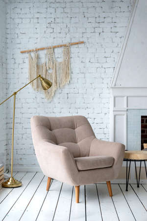 1 beige armchair in a bright room against a white wall, fireplace 免版税图像