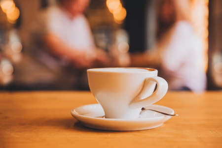 1 Cup with saucer and spoon on a brown wooden table in a cafe