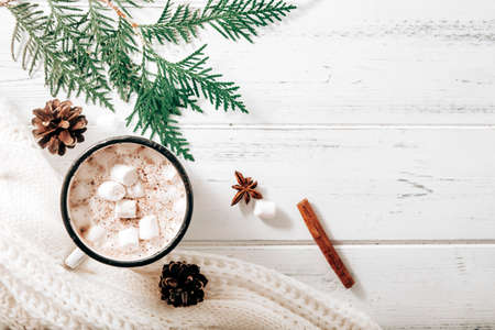 hot chocolate, cocoa mug with marshmallows, white sweater, fir branches, cones, cinnamon sticks, star anise on a white wooden background, hot winter drink, place for inscription