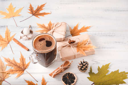 Cup of black coffee, cinnamon sticks, a slice of dried orange, a gift box, fall yellow maple leaves, cones on a white wooden background, autumn,