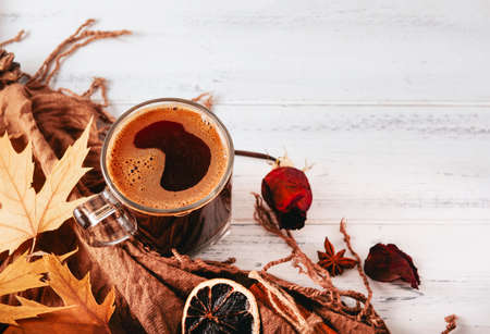 1 Cup of black coffee with a brown scarf and maple leaves and sticks of cinnamon, dried rose, a slice of dry orange on a white wooden background