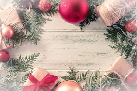 fir branches, red and gold Christmas balls, boxes with gifts, thuja, a reel with a rope, a place for writing on a white wooden background