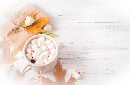 1 mug of hot chocolate with marshmallows, maple yellow dry leaves, gift box, white flowers on a white wooden background