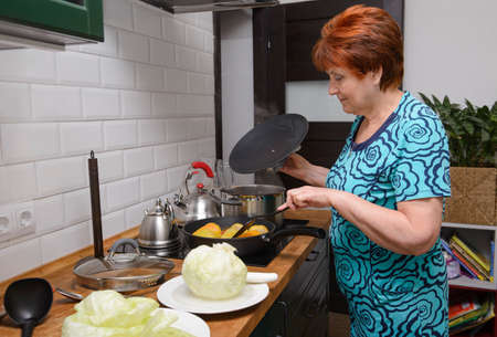 1 adult woman in the kitchen preparing stuffed peppers and cabbage