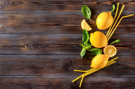 several yellow whole lemons and slices, sprigs of green Basil, yellow tubes on a dark wooden background 免版税图像