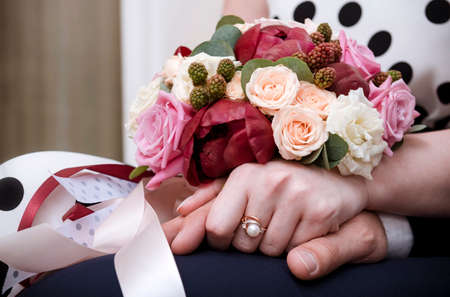 bride and groom hold hands, bride bouquet of maroon and white roses, beautiful flowers