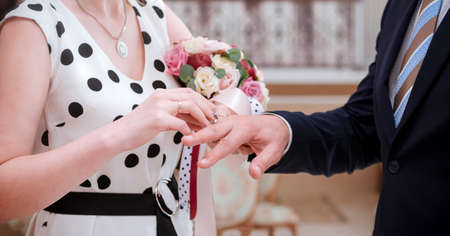 bride in a dress with a bouquet puts a ring on the finger of the groom in a suit