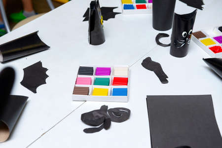 multi colored plasticine, children's crafts made of black paper, preparation for the holiday, Halloween