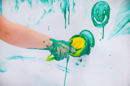 child draws green paint on a white wall, childrens creativity