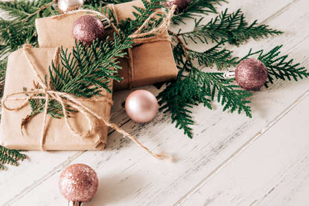 boxes with gifts on spruce branches, pink Christmas balls on a white wooden background, Christmas still life,