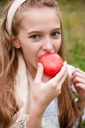 1 white girl 11 years old eats a fresh red tomato 免版税图像