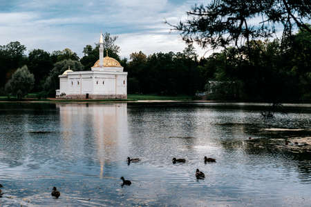 white pavilion in Oriental style in a Park on the Bank of a pond with ducks on a background of greenery on a cloudy day, Saint Petersburg