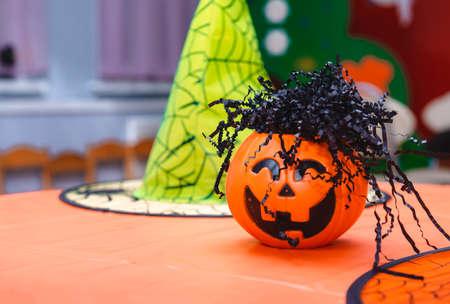 1 orange pumpkin, yellow witch hats on the table 免版税图像