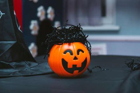 orange pumpkin on the table, black witch hat on a dark background