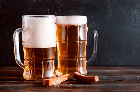 2 mugs of light beer with foam and snacks, croutons on a dark wooden background 免版税图像