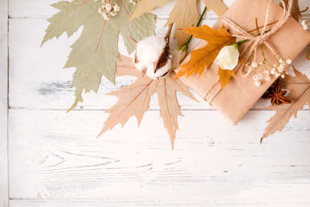 gift, dry maple leaves, white flowers on a white wooden background, copy space