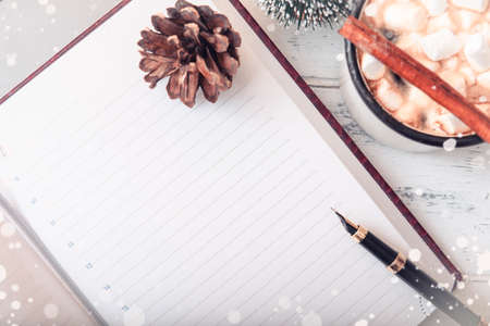 blank sheet of Notepad with a fountain pen, a cone, a mug of hot chocolate with marshmallows and cinnamon