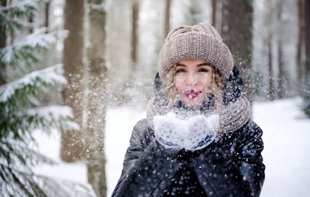 1 white blonde woman in a black jacket and hat and mittens in the forest in winter blowing on the snow on her hands