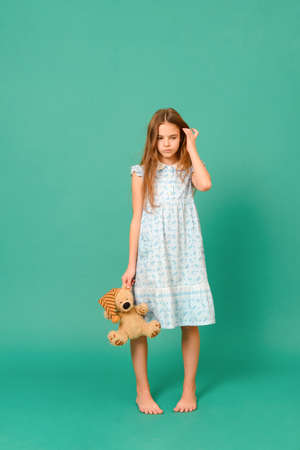 1 sad white teenage girl 10 years old in a blue dress holding a toy bear on a green background