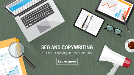 Seo and copywriting concept desk with computer, tablet, megaphone and magnifier
