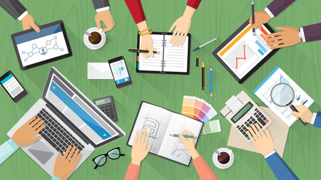 Creative team desktop top view with computer, tablets, stationery and people working together