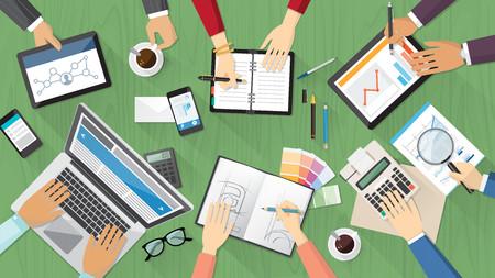 Creatieve team desktop bovenaanzicht met computer, tablets, briefpapier en mensen samen te werken