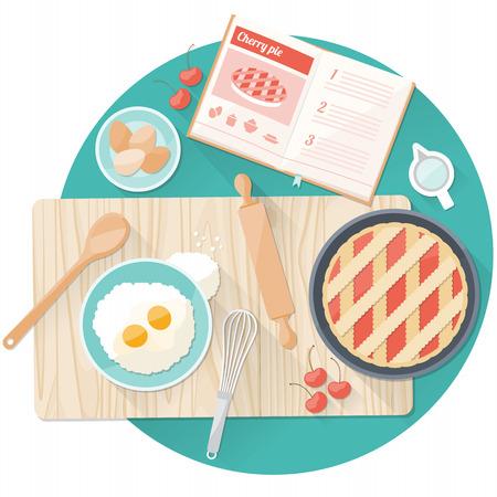 Kitchen worktop top view with utensils, open cookbook and cherry pie preparation