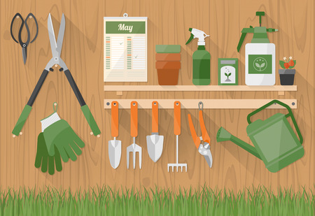 Gardening tools and products on a wooden shelf and hanging on a wall with grass at bottom, hobby and diy concept