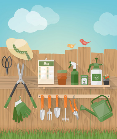gardening tools: Gardening and diy hobby garden with wooden fence with tools hanging, plants and birds, grass at bottom