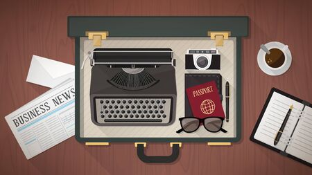Reporter and writer vintage open suitcase with a typewriter, camera, passport, organizer and newspaper, top view
