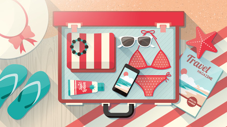 open magazine: Holidays on the beach concept, fashion female accessories in a open suitcase, bikini, sunglasses, hat and mobile phone in an open vintage suitcase on wooden flooring and sand
