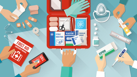 at first: First aid kit with medications and emergency equipment and medical team hands
