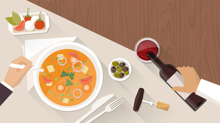 table top: Fine dining at restaurant, a customer is eating a tasty soup and a waiter is pouring wine in a glass