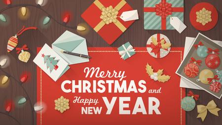 motivos navideños: Preparación para la bandera de la Navidad, vista superior mesa de madera con cajas de regalo, cintas, luces y adornos navideños, el texto en el centro