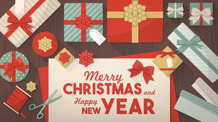 feestelijk: Voorbereiden voor Kerst en het verpakken van geschenken, inpakpapier rollen, geschenkdozen, schaar en linten op een bureau, bovenaanzicht