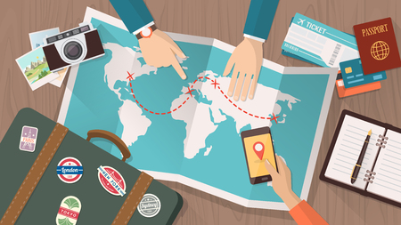 Couple planning a trip around the world, he is pointing on a map and she is using a mobile app, vacations and holidays concept