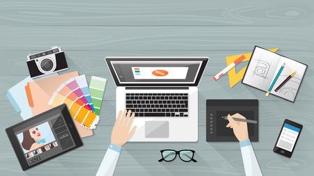 Profesjonalne kreatywny grafik pracy przy biurku, on jest projektowanie ilustracji wektorowych za pomocą laptopa