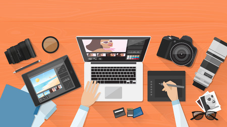 Fotografo professionista che lavora alla scrivania in ufficio, si sta modificando le sue immagini utilizzando un computer portatile e una tavoletta grafica Vettoriali