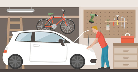 Home garage with car, bike and tools hanging on the wall, a man is repairing the car