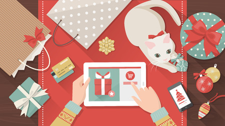 holiday gifts: Woman purchasing Christmas gifts online using a tablet, her cat is playing with a bauble on the desk, holiday and celebrations banner