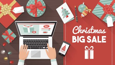 man using laptop: Man purchasing Christmas gifts online using a laptop on his desk, shopping bags and decorations all around, holiday and celebrations banner