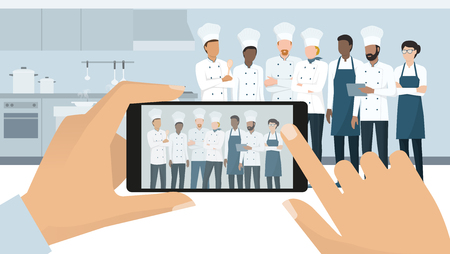 Professional chefs posing in the restaurant kitchen, a man is taking a picture using a smartphone, subjective point of view