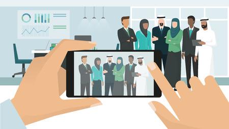 Pessoas de negócios árabes muçulmanos posando juntos e reunião em um prédio de escritórios corporativos, um homem está tirando uma foto usando um smartphone