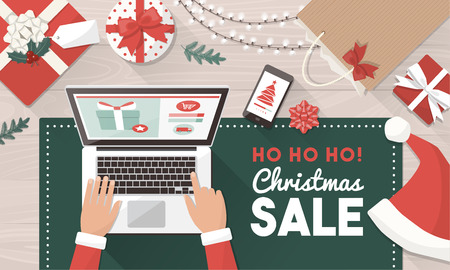 Santa ordering Christmas gifts online and connecting with his laptop: Christmas holiday sale and online shopping concept