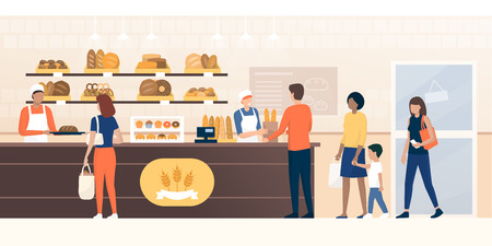 People shopping in the bakery and shop assistants working and selling fresh bread to the customers