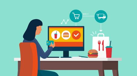 Woman connecting with her computer at home and ordering fast food at home, she is paying with a credit card