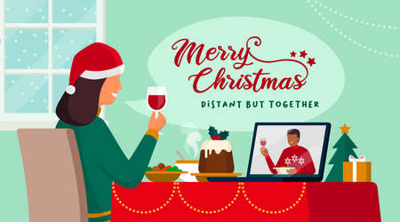Couple celebrating Christmas on a video call, they are eating and toasting together, coronavirus covid-19 social distancing