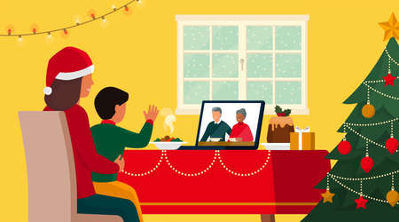 Families celebrating Christmas at home and connecting online on video call, the child is waving at the grandparents on the laptop screen while having lunch