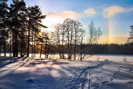 atmospheric phenomena: Winter landscape. Sun halo. Parhelion. Tracks on the snow. Frozen lake