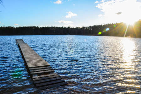 Flooded wooden bridge in the lue, waving lake water and shining sun.